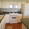 Electric range, microwave, coffee maker, dishwasher, island counter.